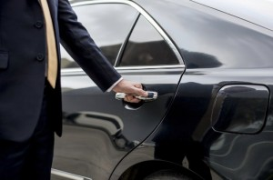Man opening the door to a limo. MBEG Limousine Service, Dallas-Fort Worth.